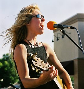 photo girl with guitar belting her song
