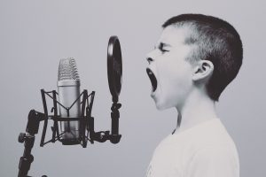 singing boy in profile belting into a studio microphone