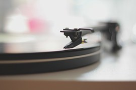 needle arm of a turntable playing a vinyl record