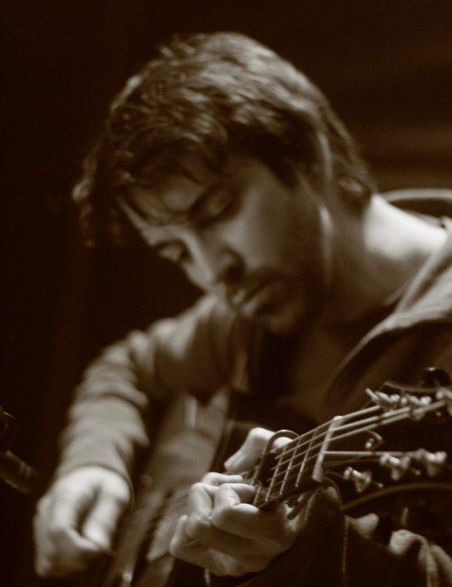Scott Dente plays acoustic guitar